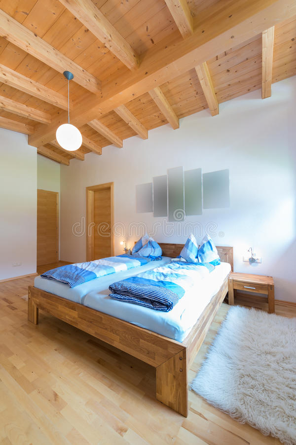 Vertical shot of wooden bed in bedroom. At timber house royalty free stock image
