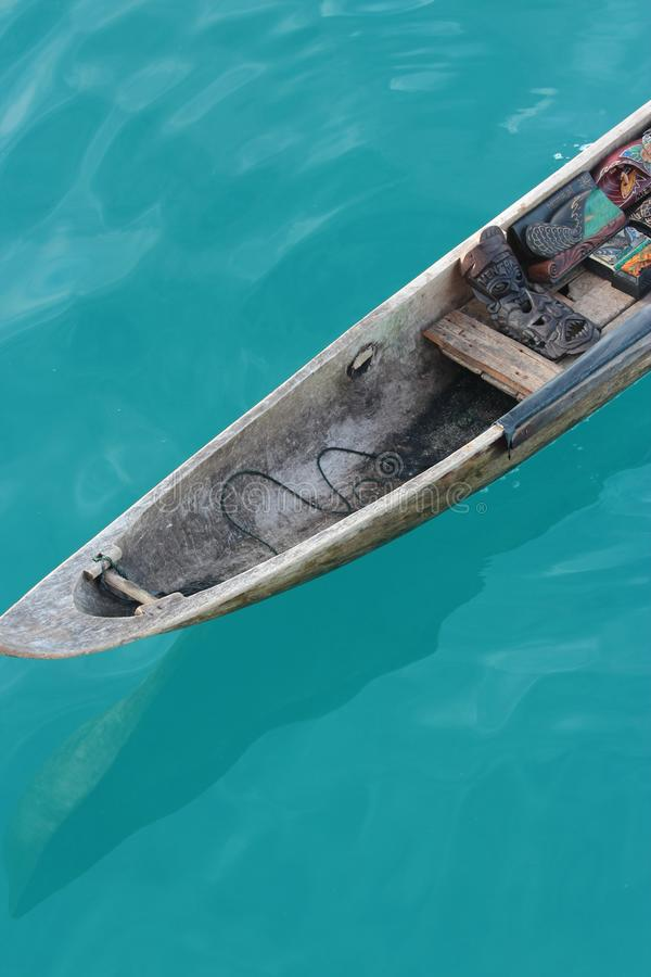 Vertical shot of a wooden canoe boat with a tribal mask on it. A vertical shot of a wooden canoe boat with a tribal mask on it royalty free stock images