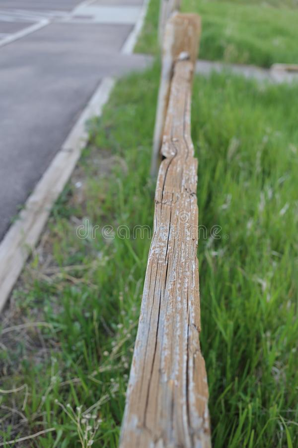 Vertical shot of a wooden fence on a  grassy field near the road. A vertical shot of a wooden fence on a  grassy field near the road royalty free stock image