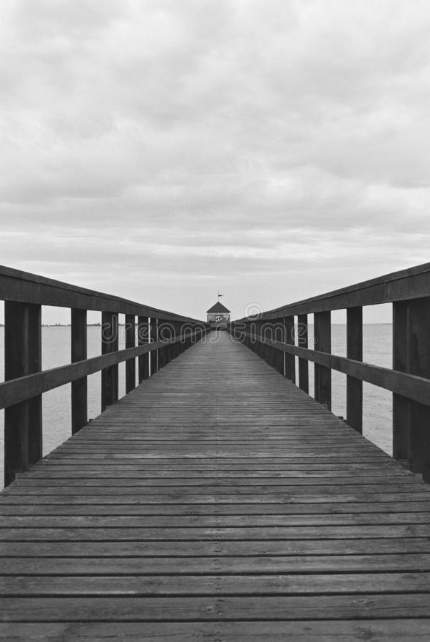 Vertical shot of a wooden pathway over the water toward a small booth in black and white. A vertical shot of a wooden pathway over the water toward a small booth stock photography