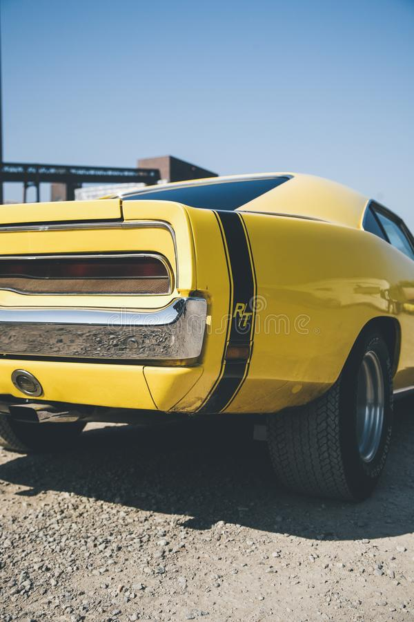 Vertical shot of a yellow muscle car at daytime with a clear sky in the background royalty free stock image