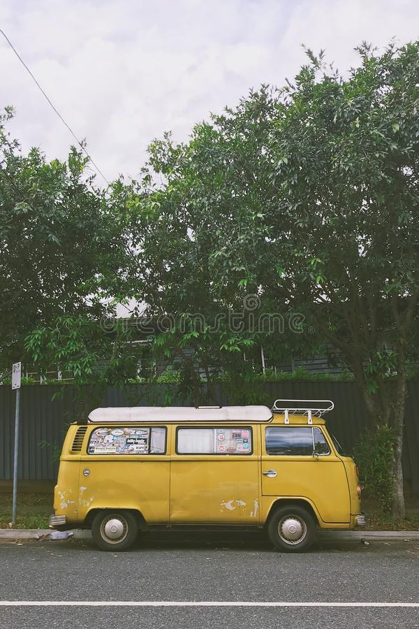 Vertical shot of a yellow van parked on a road near trees. A vertical shot of a yellow van parked on a road near trees stock photography