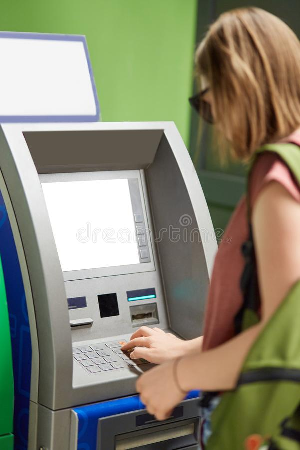 Vertical shot of young fashionable girl stands back near cash machine, withdraws money, types on buttons after inserting credit ca stock images