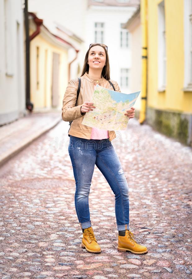 Vertical shot of young happy woman holding map. Smiling traveler sightseeing in city. Tourist with backpack looking directions. Travel and navigation concept royalty free stock photo