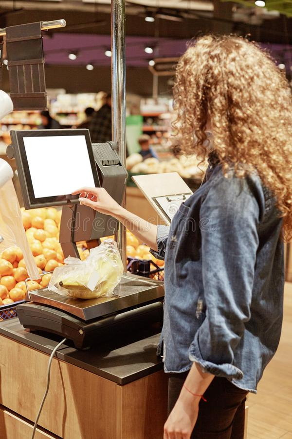 Vertical shot of young woman weighs bananas on electronic scales with touch screen, buys fruits in supermarket, stands back to cam stock photography