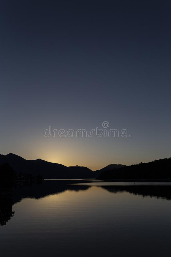 Vertical silhouette shot of mountains by the body of water during sunset. A vertical silhouette shot of mountains by the body of water during sunset royalty free stock image