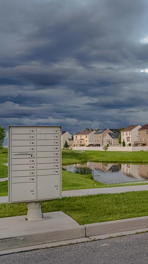 Vertical Sky filled with gray clouds over homes and pond amid a vast grassy terrain. White metal cluster mailbox at the side of a road can be seen in the royalty free stock image