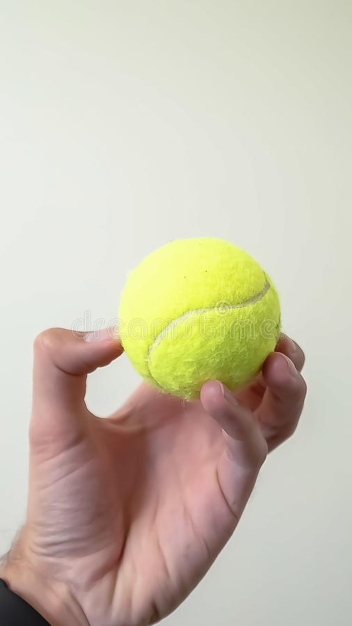 Vertical Small ball held by a hand isolated against a white wall and ceiling background royalty free stock images