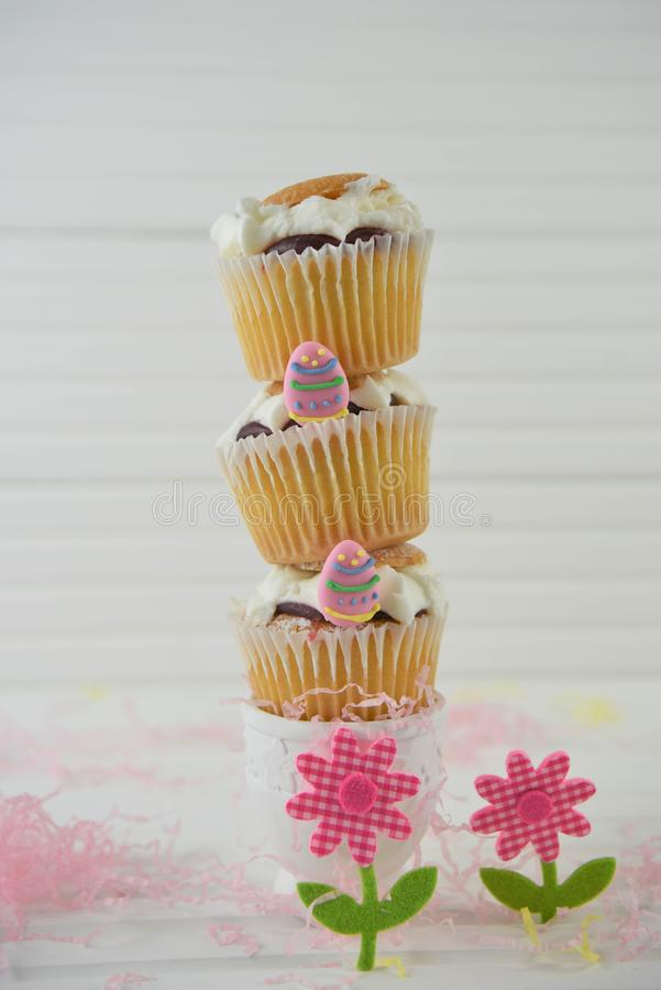 Vertical stack of mini Easter cakes on white. Cream jam and vanilla homemade cupcakes or fairy cakes with sprinkles. Stacked in a vertical heap with Easter iced royalty free stock photo