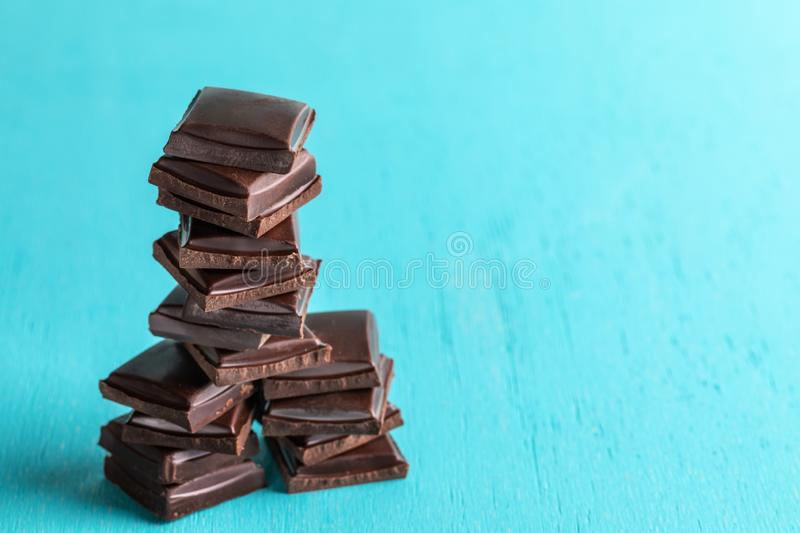 Vertical stack of squared slices of chocolate on turquoise  background. stock photo