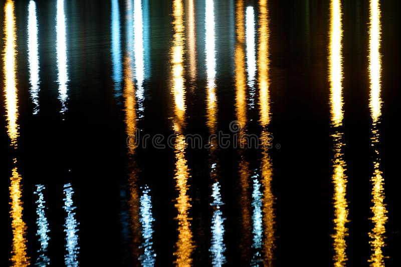 Vertical strips of reflected light at night stock image
