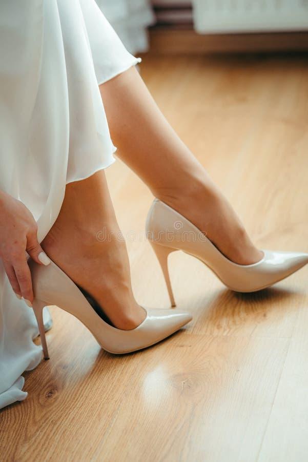 Vertical strzał czułe ręki panna młoda stawia na białych ślubnych szpilkach obraz royalty free