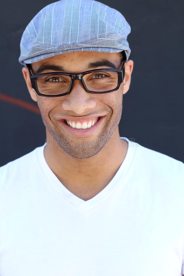 Vertical studio portrait of young black man casual v-neck style wearing vintage glasses and hat isolated against dark background stock photography