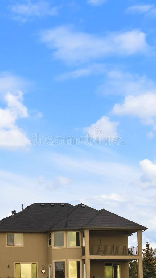 Vertical Three storey home with porch and balcony against blue sky with bright clouds. Coniferous trees and snow covered ground can be seen outside the house royalty free stock photos