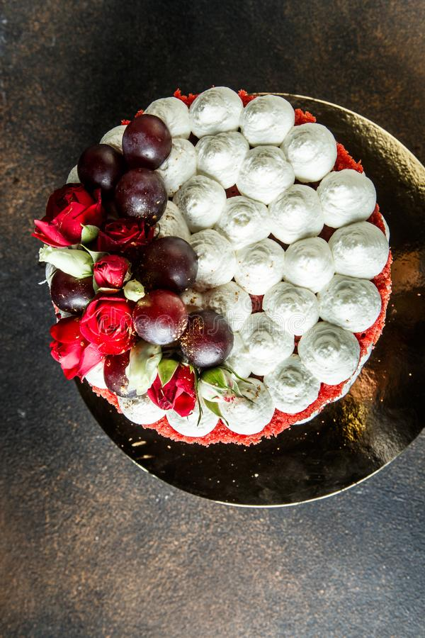 Vertical top view of cake decorated with bizet, grapes and roses. Vertical top view of beautiful cake decorated with white bizet, grapes and roses royalty free stock images