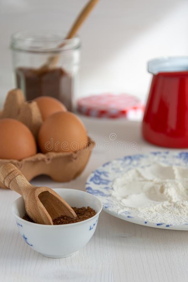 Vertical top view of ingredients for pastries, brown sugar, flour, eggs and red saucepan stock images