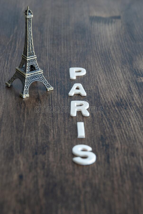 Vertical top view of mockup of the Eiffel tower with Paris letters on dark wood background royalty free stock photography