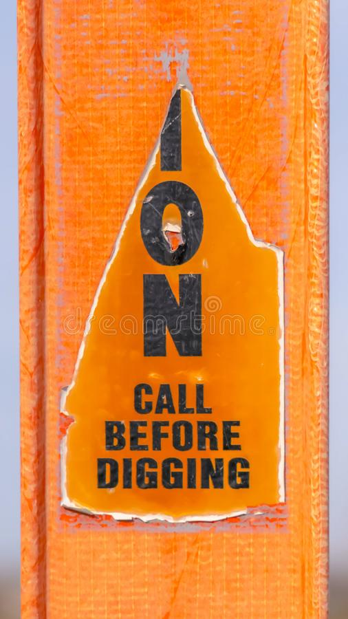 Vertical A torn Caution sign on a bright orange post against a blurry background royalty free stock images