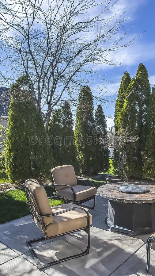 Vertical Upholstered metal chairs and round table at the patio of a home under blue sky royalty free stock photo