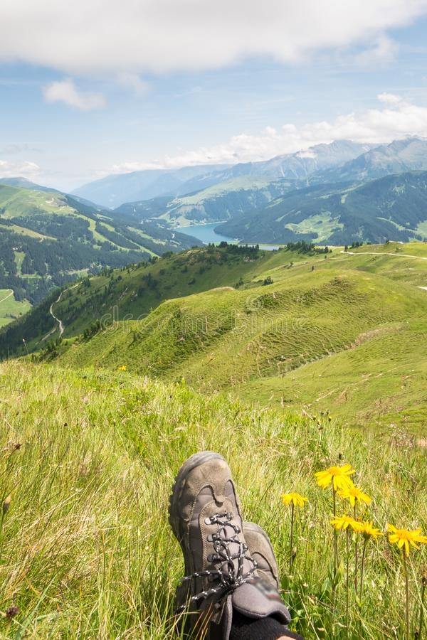 Hiking boots of a hiker who is resting in the majestic mountain landscape of the Alps stock photography