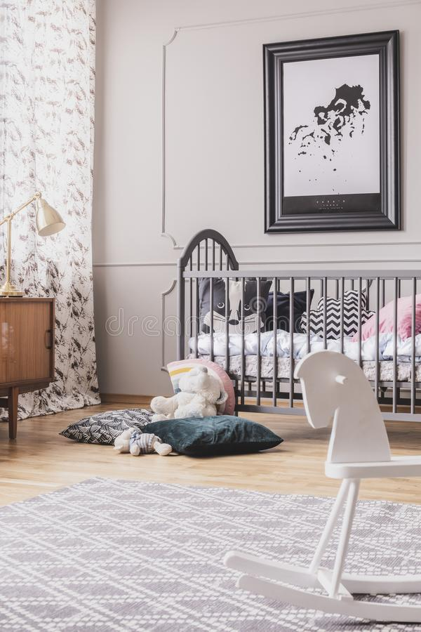 Vertical view of black and white map in frame above wooden crib with pillows, real photo with carpet on the wooden floor. Concept stock photography