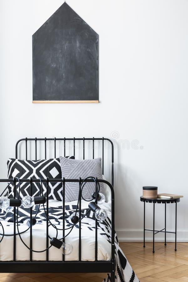 Blackboard on the wall of teenagers bedroom with black and white patterned bedding on single metal bed, real. Vertical view of blackboard on the wall of stock photo