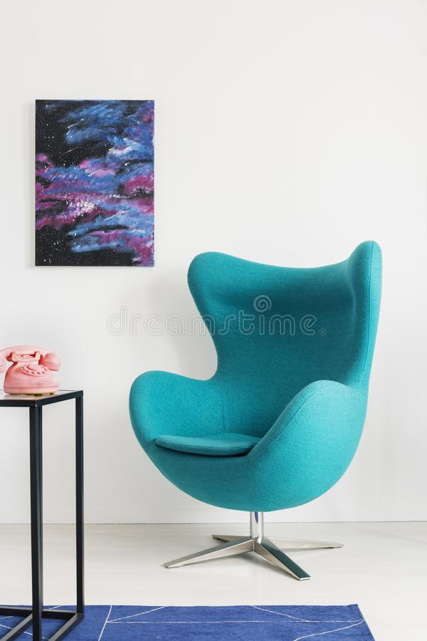 Vertical view of blue egg chair next to metal shelf with pink telephone, cosmos graphic on the wall, real photo with copy space royalty free stock photo
