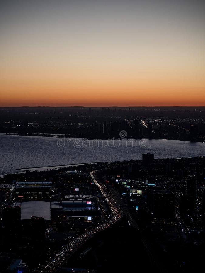 Vertical view from cn tower to toronto downtown during dawn sunset with highway and traffic jam royalty free stock image