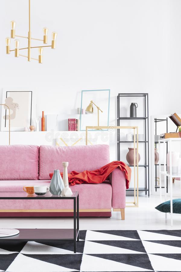 Vertical view of coffee table next to powder pink sofa in art collector`s apartment stock photography
