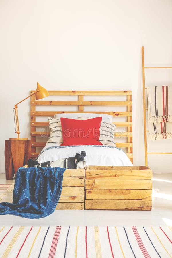 Vertical view of comfortable bed with wooden headboard, red pillow and bright bedding, bedroom interior with copy space on the whi royalty free stock image