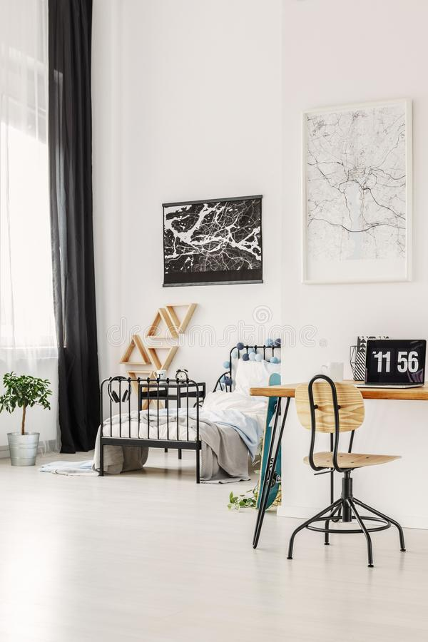 Comfortable workspace with laptop and map in fashionable teenager`s bedroom. Vertical view of comfortable workspace with laptop and map in fashionable teenager`s royalty free stock image