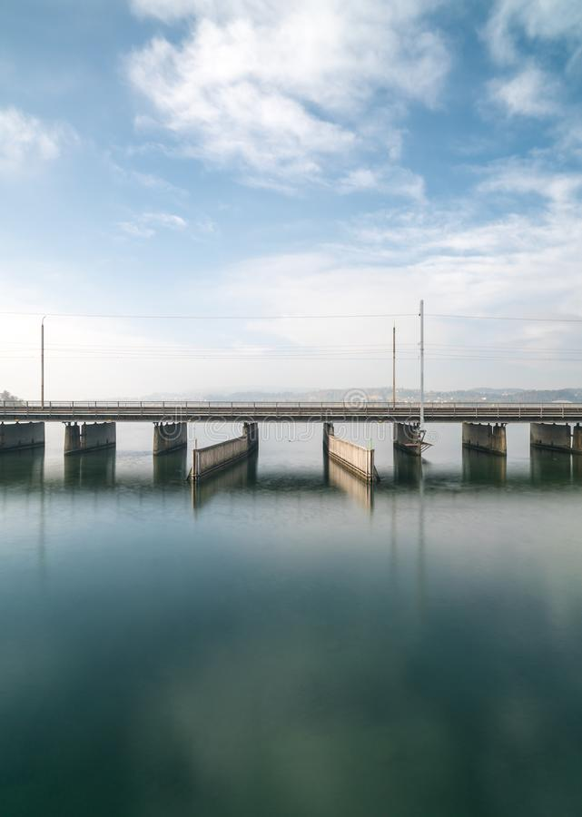 Vertical view of a concrete bridge over water with a train line and road running parallel and a boat and ship passageway below royalty free stock photo