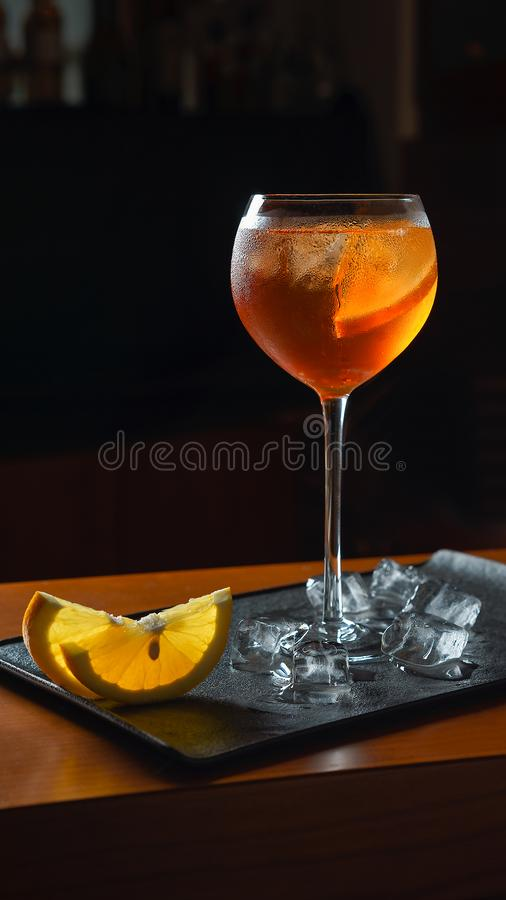 Cool drink cocktail Aperol Spritz with orange slices and ice on black tray. Vertical view on cool cocktail Aperol Spritz with orange slices and ice on black tray royalty free stock photography