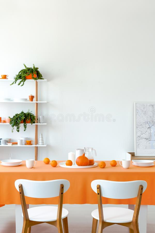 Vertical view of dining room table set for dinner. White plates and mugs on orange tablecloth. Shelf with tableware and plants behind it stock photo