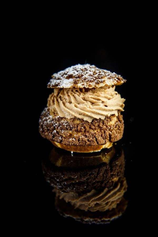 Vertical view on french dessert shoo served on on black background. Vertical view on french dessert shoo with caramel cream filling served on black mirror royalty free stock images