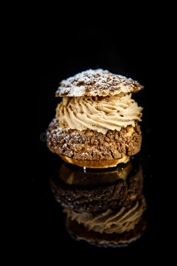 Vertical view on french dessert shoo served on on black background. Vertical view on french dessert shoo with caramel cream filling served on black mirror stock photo