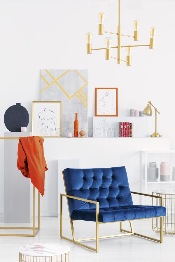 Golden chandelier above petrol blue settee in white modern art collector`s apartment, real photo. Vertical view of golden chandelier above petrol blue settee in stock photo