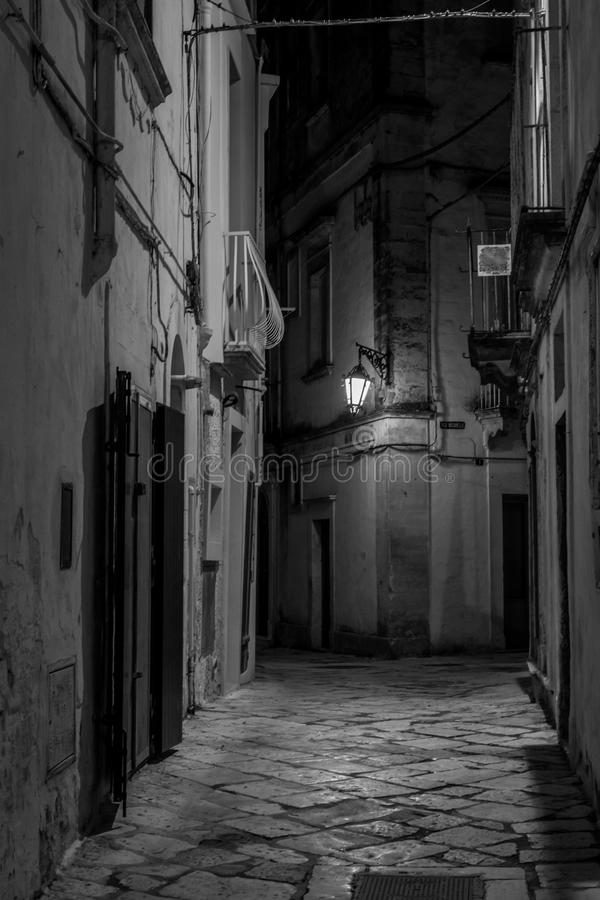 Vertical View in Greyscale of a Street Illuminated By Artificial. Vertical View of a Street Illuminated By Artificial Light at Night. City of Martina Franca royalty free stock photos