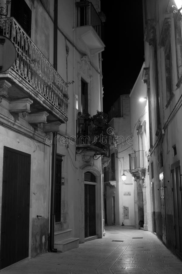 Vertical View in Greyscale of a Street Illuminated By Artificial. Vertical View of a Street Illuminated By Artificial Light at Night. City of Martina Franca stock photography