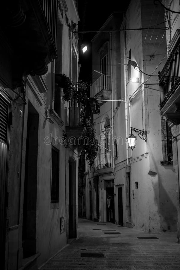 Vertical View in Greyscale of a Street Illuminated By Artificial. Vertical View of a Street Illuminated By Artificial Light at Night. City of Martina Franca stock image