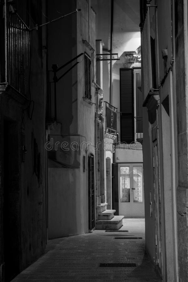 Vertical View in Greyscale of a Street Illuminated By Artificial. Vertical View of a Street Illuminated By Artificial Light at Night. City of Martina Franca royalty free stock photography