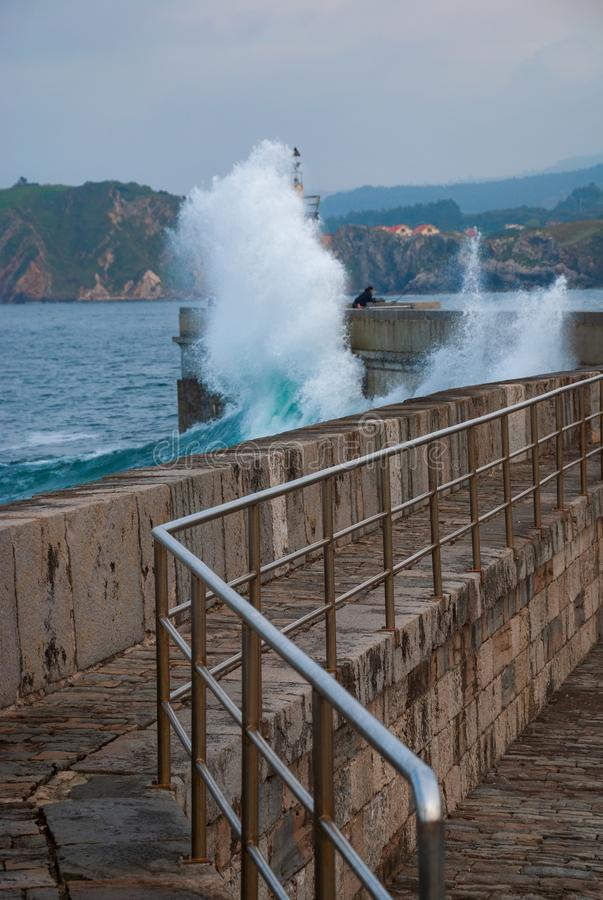 Vertical view of harbor pier with breaking waves and fisherman in the background. In Comillas, Cantabria, Spain, Europe stock photo