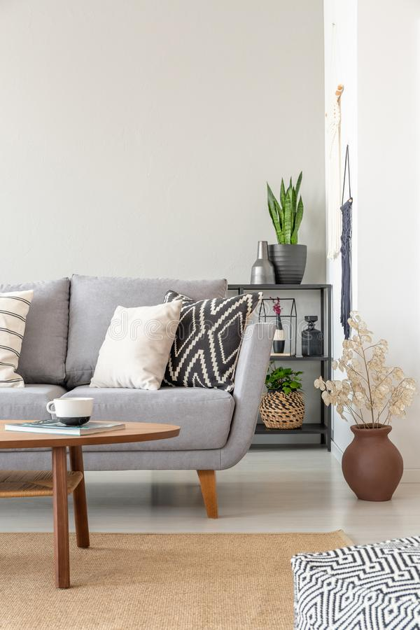 Industrial living room with grey couch with patterned pillows, real photo with copy space on the wall. Vertical view of industrial living room with grey couch stock images