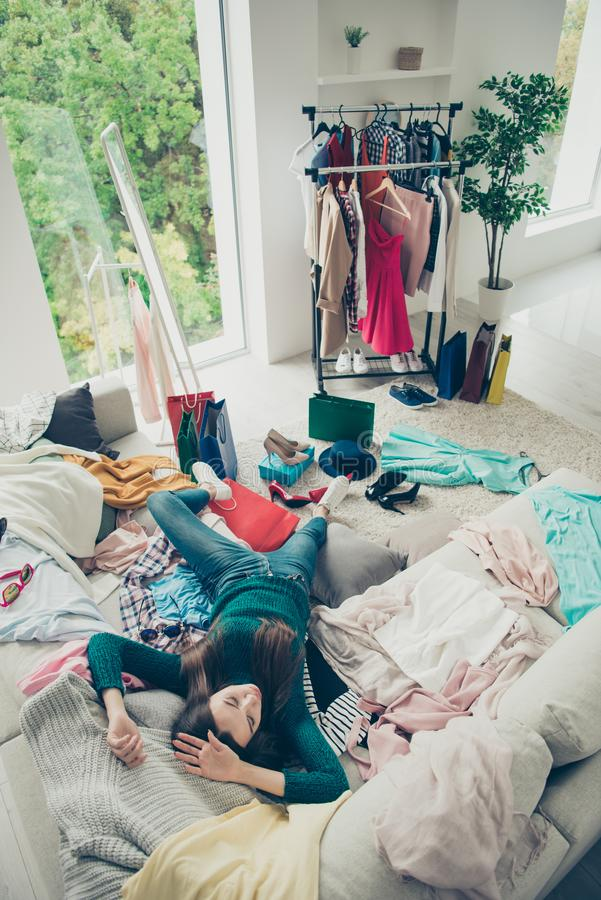 Vertical view of nice attractive pretty bored tired girl student lying on divan among different things preparing for. Event prom date in light white interior royalty free stock photos