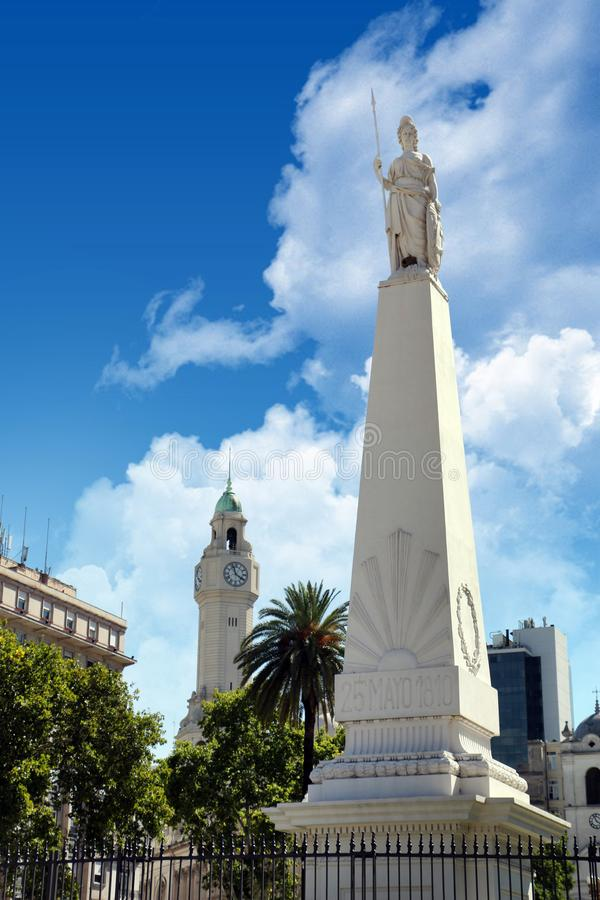 Vertical view of The Piramide de Mayo in Buenos Aires, Argentina, surrounded by old buildings and green palm trees royalty free stock photos