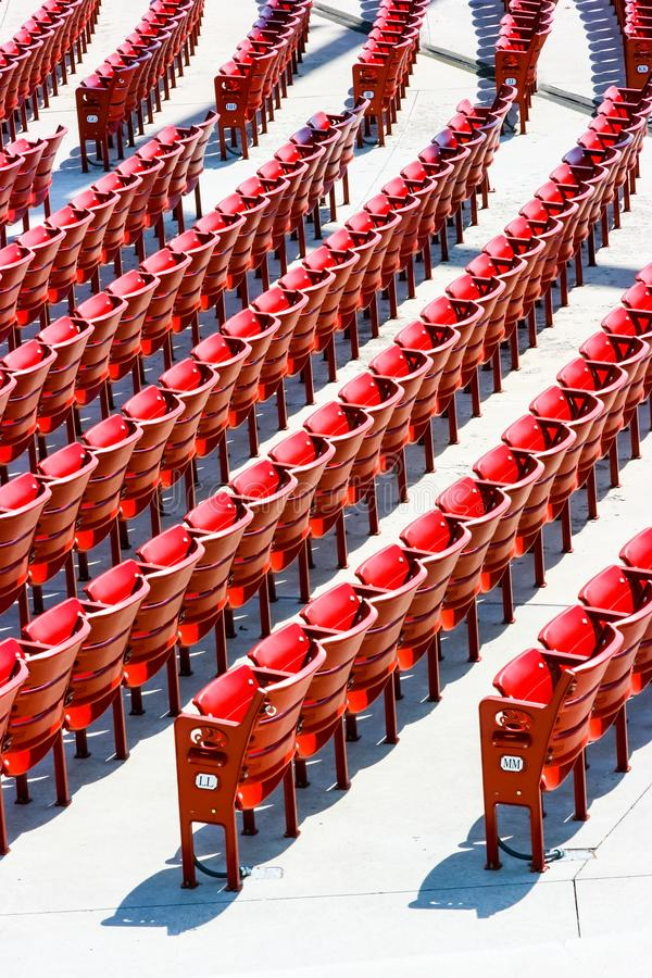 Vertical view of red plastic seats in rows stock photography