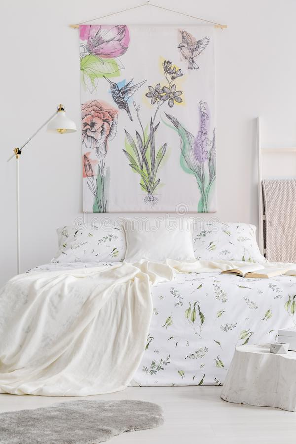 Vertical view of a scandinavian style bedroom interior with a bed dressed in white linen with painted green plants. Fabric wall ar. T with colorful birds and royalty free stock photography