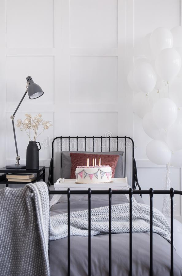 Single metal bed with grey bedding and burgundy pillow, birthday cake with candles on white trey, real photo with royalty free stock photos