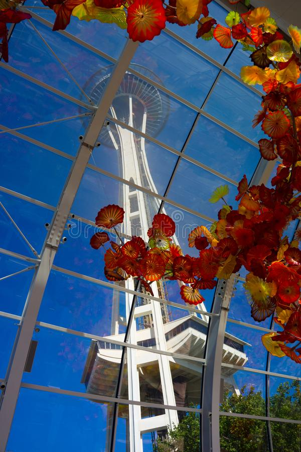 Vertical view Space Needle through Chihuly glass exhibit against blue sky stock images
