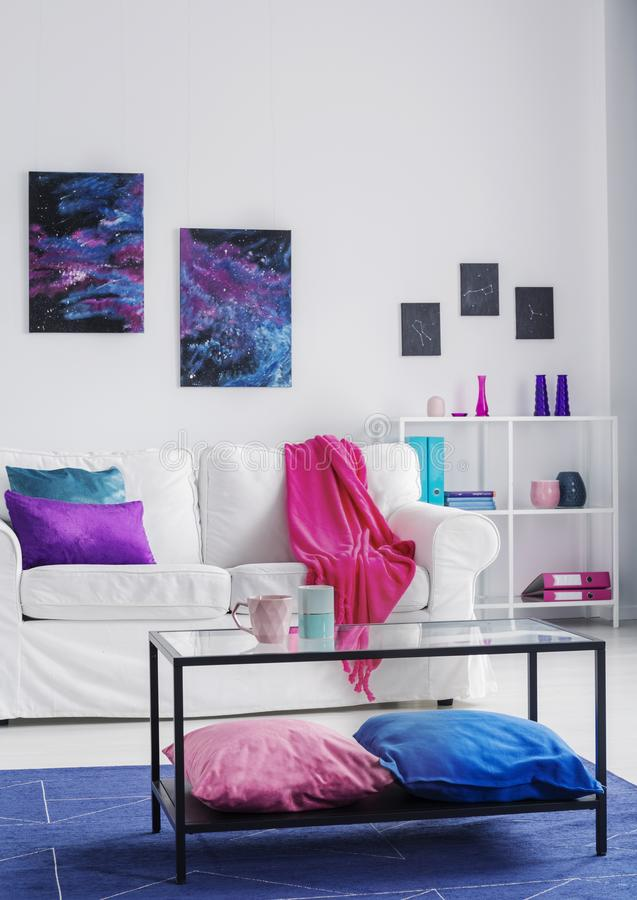 Vertical view of stylish living room with comfortable white couch with pink blanket and blue and purple pillows, cosmos graphics o. N the wall, real photo stock image